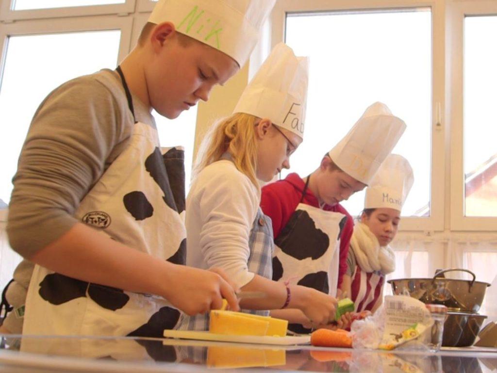 Kinder mit Kochmützen schnippeln Gemüse