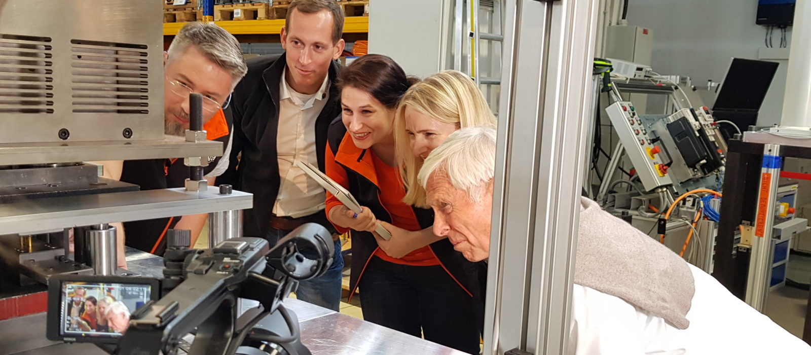 Drehsituation: Vier Personen beugen sich vor um eine Maschine ganz genau anschauen zu können